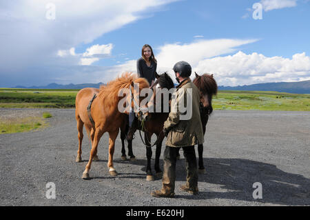 Tourist visiting Iceland getting the chance to ride an Icelanic pony with a local farmer. - Stock Photo