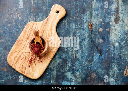 Saffron in olive wood bowl on blue wooden background - Stock Photo