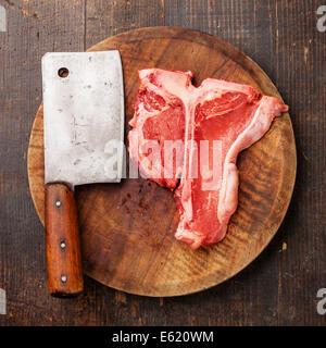 Raw fresh meat T-Bone Steak and meat cleaver on dark background - Stock Photo