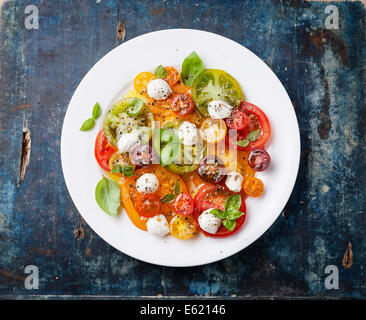 Colorful tomatoes salad with mozarella on blue wooden background - Stock Photo