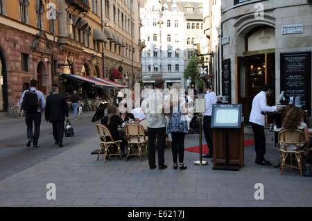 Street life in old Stockholm with sidewalk restaurants, coffee shops, pedestrians and musicians along cobblestone - Stock Photo