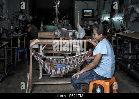 Thai mother and young child in a makeshift hammock at the family tailoring workshop. Thailand S. E. Asia - Stock Photo