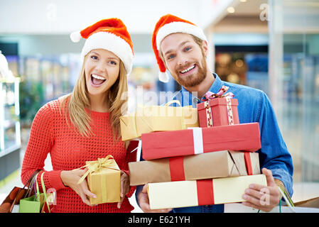 Happy couple posing with Christmas presents - Stock Photo