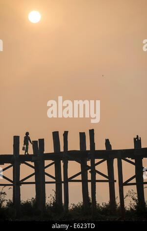 Locals on a teak bridge, U Bein Bridge over Taungthaman Lake at sunrise, Amarapura, Mandalay Division, Myanmar - Stock Photo