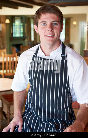 Chef Wearing Whites And Apron Sitting In Restaurant - Stock Photo