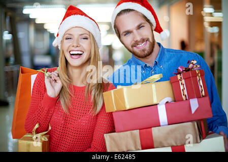 Portrait of happy couple with Christmas presents - Stock Photo