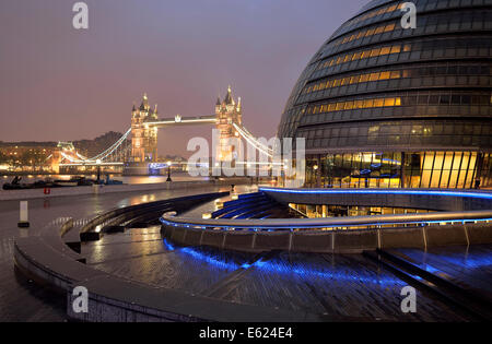 City Hall designed by Sir Norman Foster, Tower Bridge at the back, at dusk, London, England, United Kingdom - Stock Photo