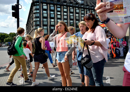 London, England, UK. Family looking at a map on Westminster Bridge - Portcullis House behind - Stock Photo