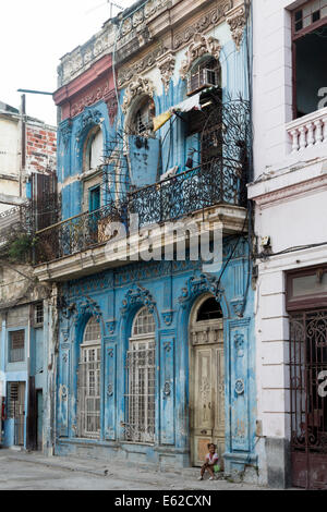 girl in front of dilapidated house on street, Old Havana, Cuba - Stock Photo