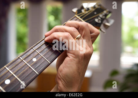 Close up of a man playing acoustic guitar showing chord fingering on the fretboard - Stock Photo