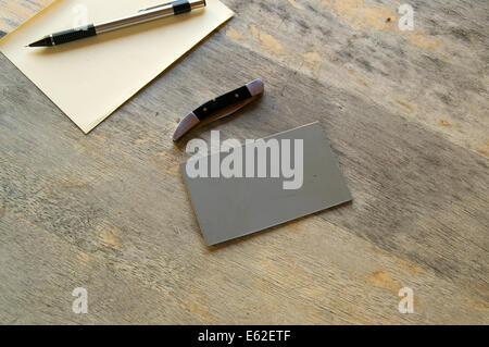 A pencil, paper, knife and grey card are seen on an old wooden table. - Stock Photo