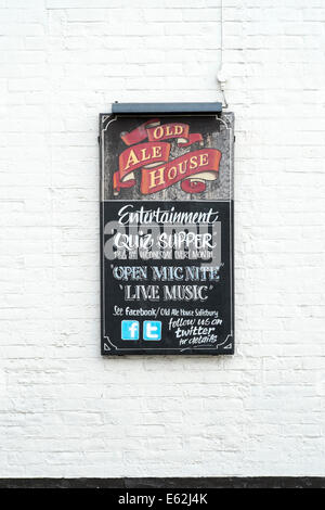 Pub chalk board on wall advertising entertainment with Facebook and Twitter symbols - Stock Photo