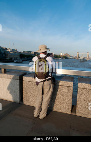 Rear view of man with rucksack standing on London Bridge looking at the River Thames and Tower Bridge London UK - Stock Photo