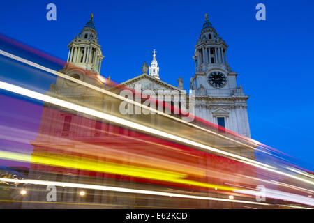 Moving red bus in front of St. Paul cathedral during twilight, London, England - Stock Photo