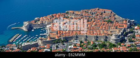 The walled city and harbour of Dubrovnik jutting out into the blue Adriatic Sea seen from the top of Mount Srd hill - Stock Photo