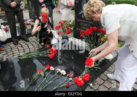 St. Petersburg. 12th Aug, 2014. People lay flowers during a ceremony in memory of soldiers who died in the Kursk - Stock Photo