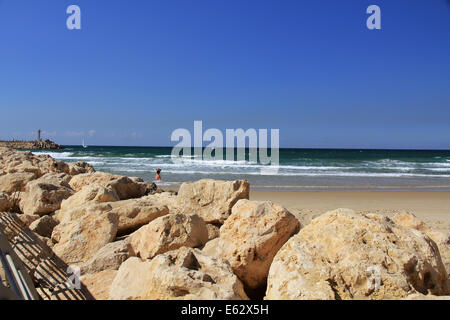 Rock sea wall with small lighthouse on the Mediterranean Sea in Herzliya Israel near Jaffa and Tel Aviv. - Stock Photo