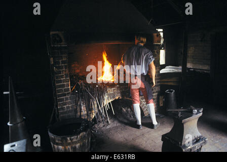 colonial blacksmith workshop. anonymous blacksmith wearing colonial clothes back to camera holding iron in forge williamsburg va usa - colonial blacksmith workshop