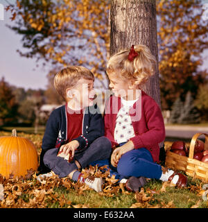 1960s BOY AND GIRL SMILING AT ONE ANOTHER SITTING UNDER AUTUMN TREE WITH APPLE BASKET AND PUMPKIN - Stock Photo