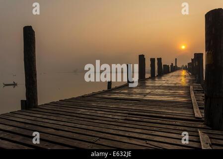 Teak bridge at sunrise, U Bein bridge across Thaungthaman Lake, Amarapura, Mandalay Division, Myanmar - Stock Photo