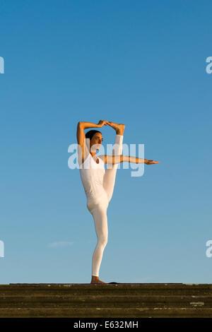 Young woman practising Hatha yoga, outdoors, showing the pose Utthita Hasta Pandangusthasana, raised hand to big - Stock Photo