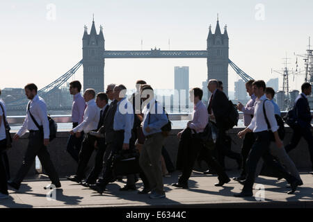 Morning commuters crossing London Bridge with Tower Bridge behind, London, England, United Kingdom, Europe - Stock Photo