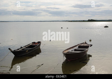 Two old wooden rowing boats tied up at the coast - Stock Photo
