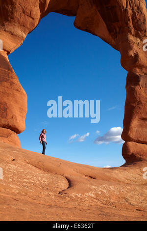 Delicate Arch (65 ft / 20 m tall iconic landmark of Utah), and tourist, Arches National Park, near Moab, Utah, USA - Stock Photo