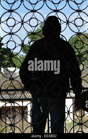 Hooded man looking at view from the balcony of an abandoned house and vintage iron gate circles pattern. - Stock Photo