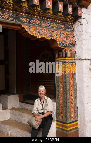 Eastern Bhutan, Lhuentse, Rinchentse Phodrang Dzong western tourist sitting under decorated door - Stock Photo