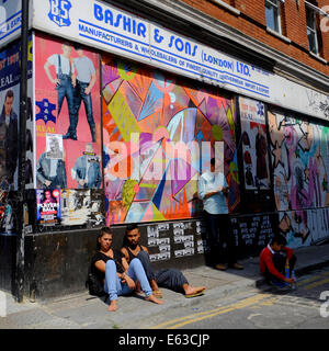 people sitting on pavement against wall on a sunny day in Shoreditch - Stock Photo