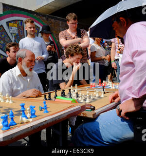 man playing chess against several opponents at the same time in Brick lane, Shoreditch, London, England - Stock Photo