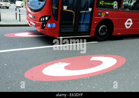 Bus passing Congestion Charge sign printed on road, Old Street Roundabout, London Borough of Islington England Britain - Stock Photo