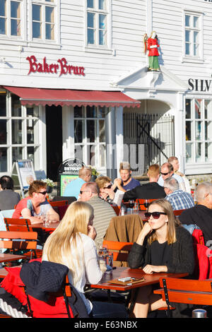 People sitting at outdoor terraces of the pubs at Bryggen wharf, Bergen, Norway - Stock Photo