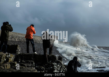 Amateur photographers jostle for position amongst onlookers to capture the huge waves breaking over Porthcawl Lighthouse. - Stock Photo