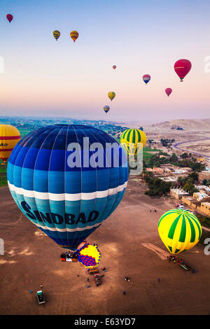 Hot air balloons flying over the West Bank of the Nile in Egypt at sunrise. - Stock Photo