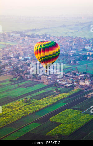 A colourful hot air balloon flies over villages on the West Bank of the Nile in Egypt. - Stock Photo