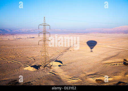The shadow of a hot air balloon and an electricity pylon over the desert of the West Bank of the Nile in Egypt at - Stock Photo