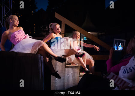 Young girl dancers sitting in the stage during the performance, while a person in the audience is making a video - Stock Photo