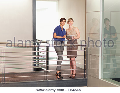 Businesswomen with digital tablet on elevated walkway in office - Stock Photo