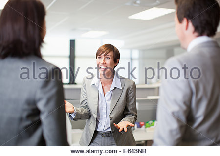 Businesswoman gesturing and talking to co-workers - Stock Photo