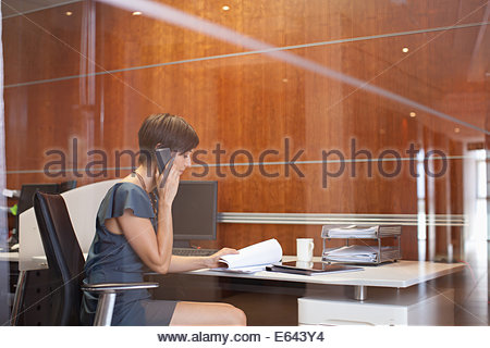 Portrait of confident businesswoman sitting at desk in office - Stock Photo