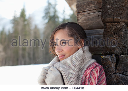 Smiling woman leaning against cabin wall in snow - Stock Photo