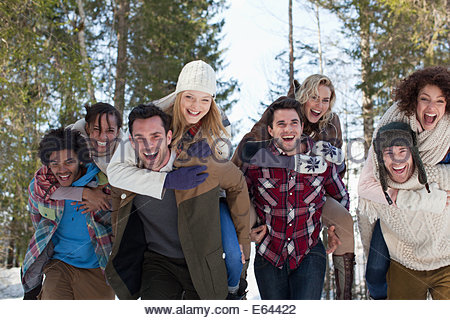 Enthusiastic couples piggybacking in snowy woods - Stock Photo