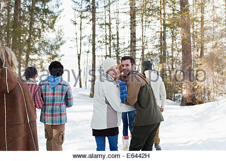 Portrait of smiling couple holding hands and walking with friends in snowy woods - Stock Photo