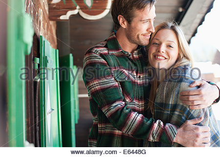 Smiling couple hugging on cabin porch - Stock Photo