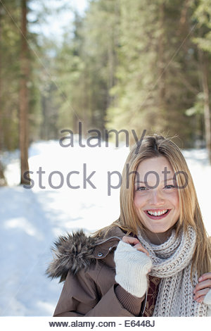 Portrait of smiling woman in snowy woods - Stock Photo
