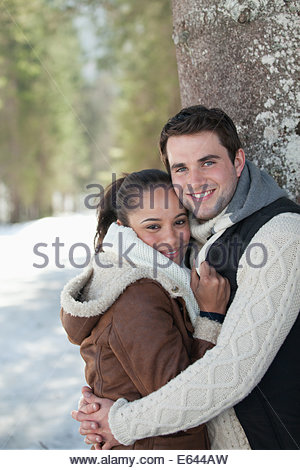 Portrait of smiling couple leaning against tree trunk in snowy woods - Stock Photo