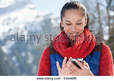 Smiling woman checking cell phone - Stock Photo