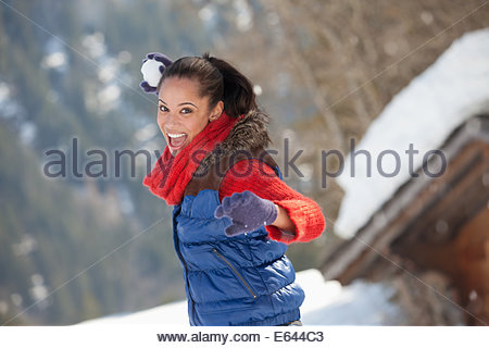 Portrait of smiling woman throwing snowball - Stock Photo